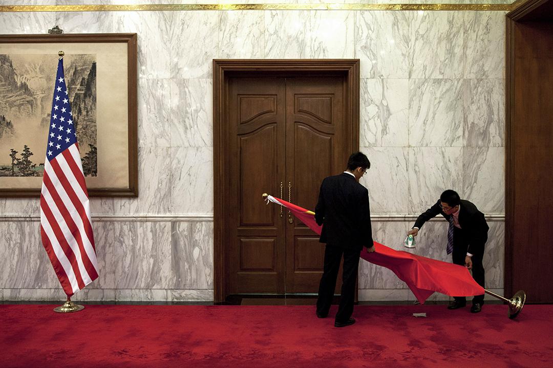 2013年5月27日,美國國家安全顧問Tom Donilon和中國國務委員楊潔在釣魚台國賓館會晤前,工作人員在中國傳統繪畫前熨一面中國國旗。