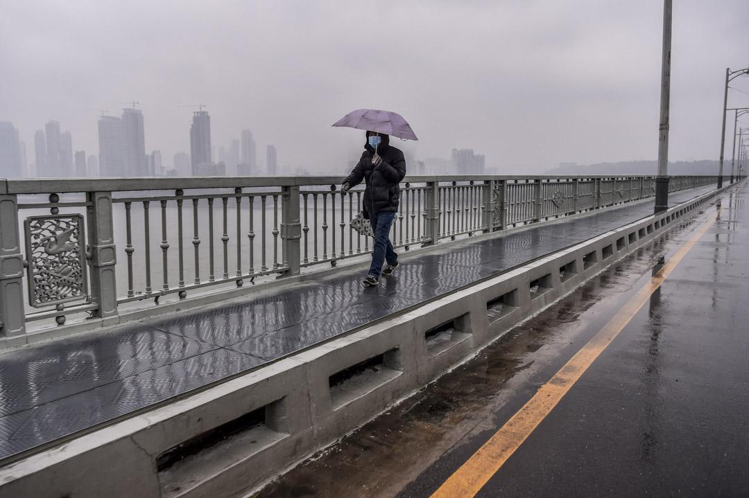 2020年1月25日,一名戴著口罩的男子在武漢的一座橋上行走。