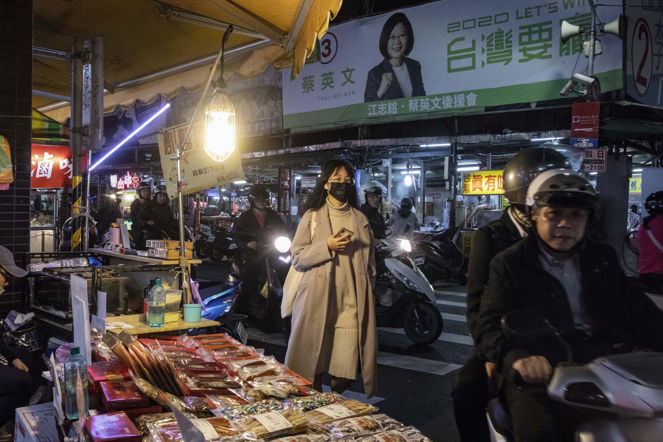 2019年12月26日,台灣內湖的夜市,市民經過一幅蔡英文的競選海報。