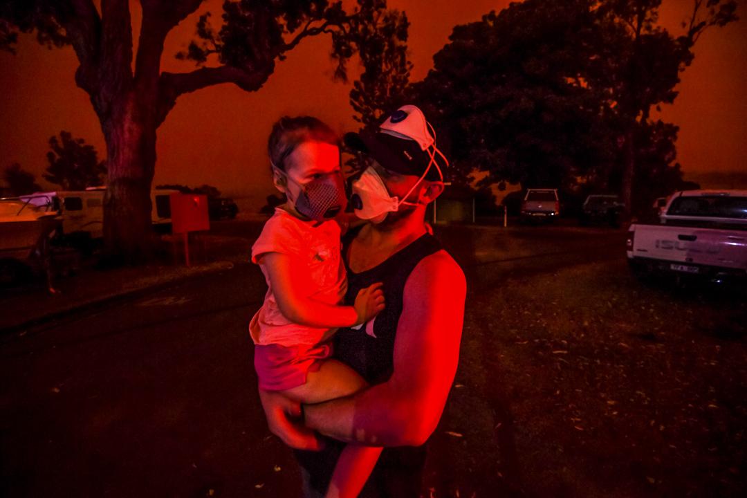 2020年1月4日,在澳洲馬拉庫塔,一個男子抱著女兒,天空因大火而染成紅色。 攝: Justin McManus/The Age/Fairfax Media via Getty Images