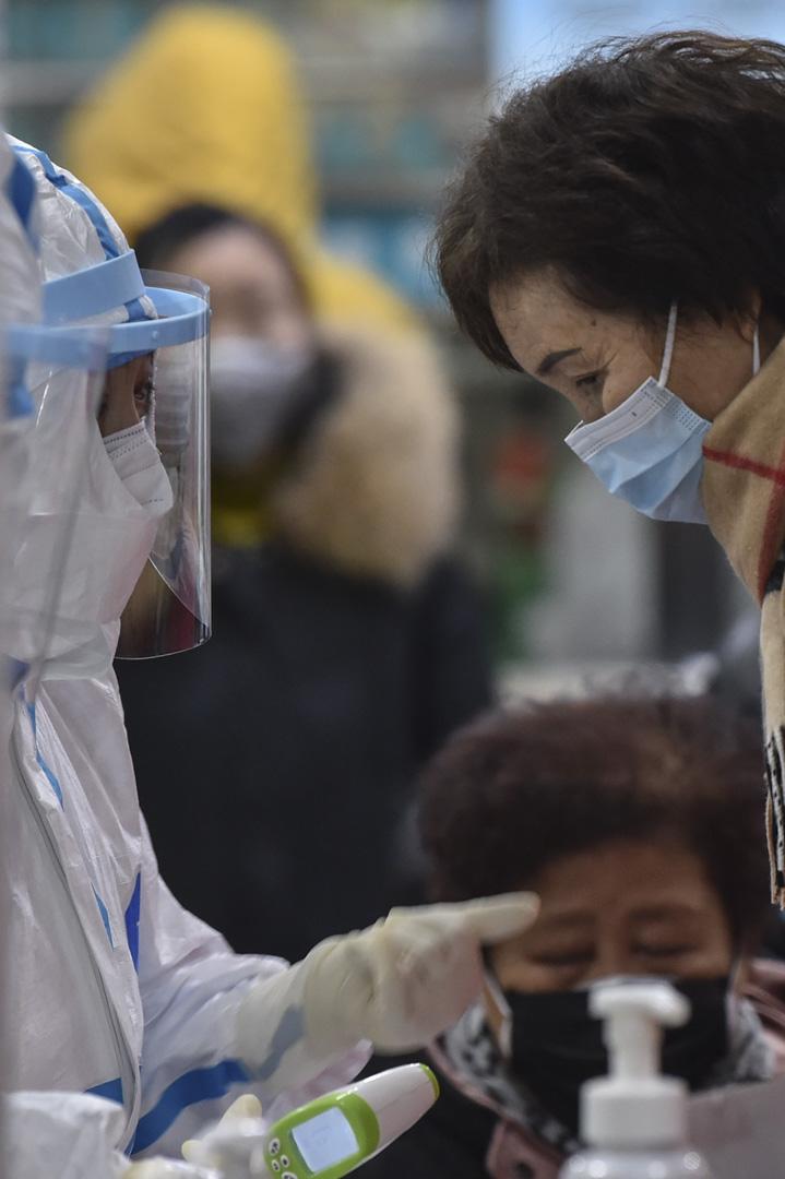 2020年1月24日,武漢紅十字會醫院的一名穿著防護衣的醫務人員,替一名婦女進行體温測量。