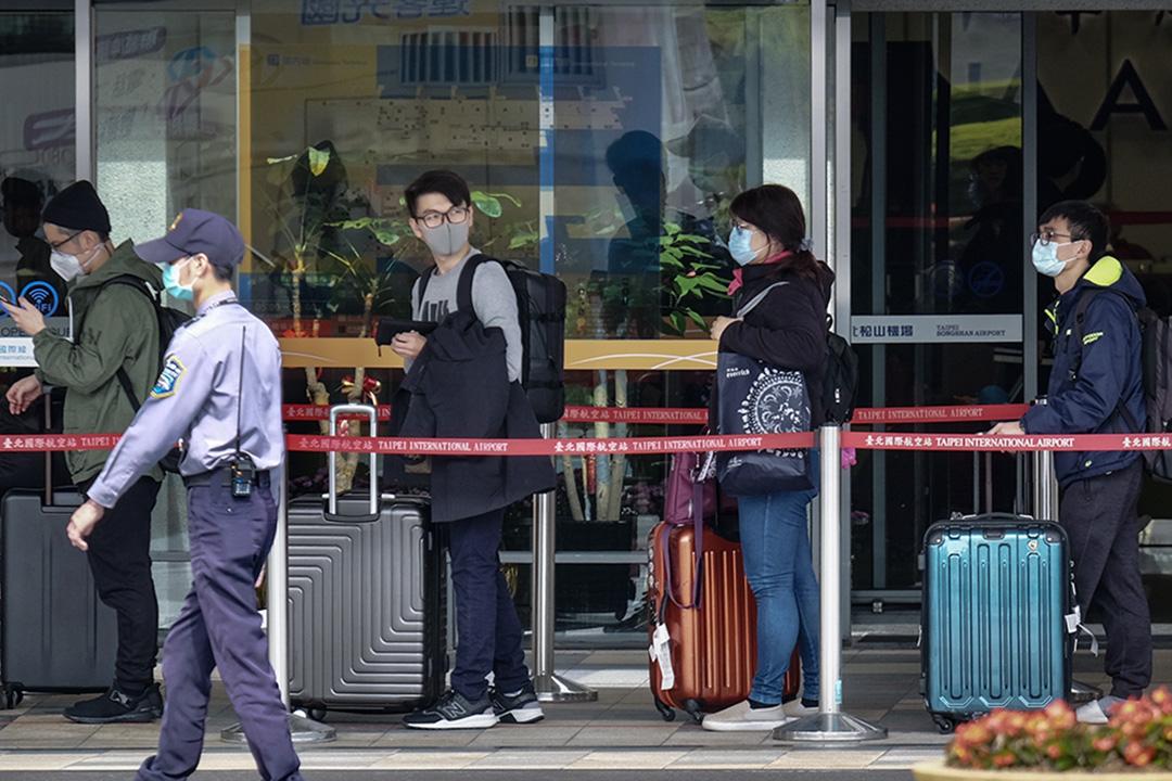 戴上口罩的乘客於2020年1月22日到達台北的松山機場。 攝:Sam Yeh/AFP via Getty Images