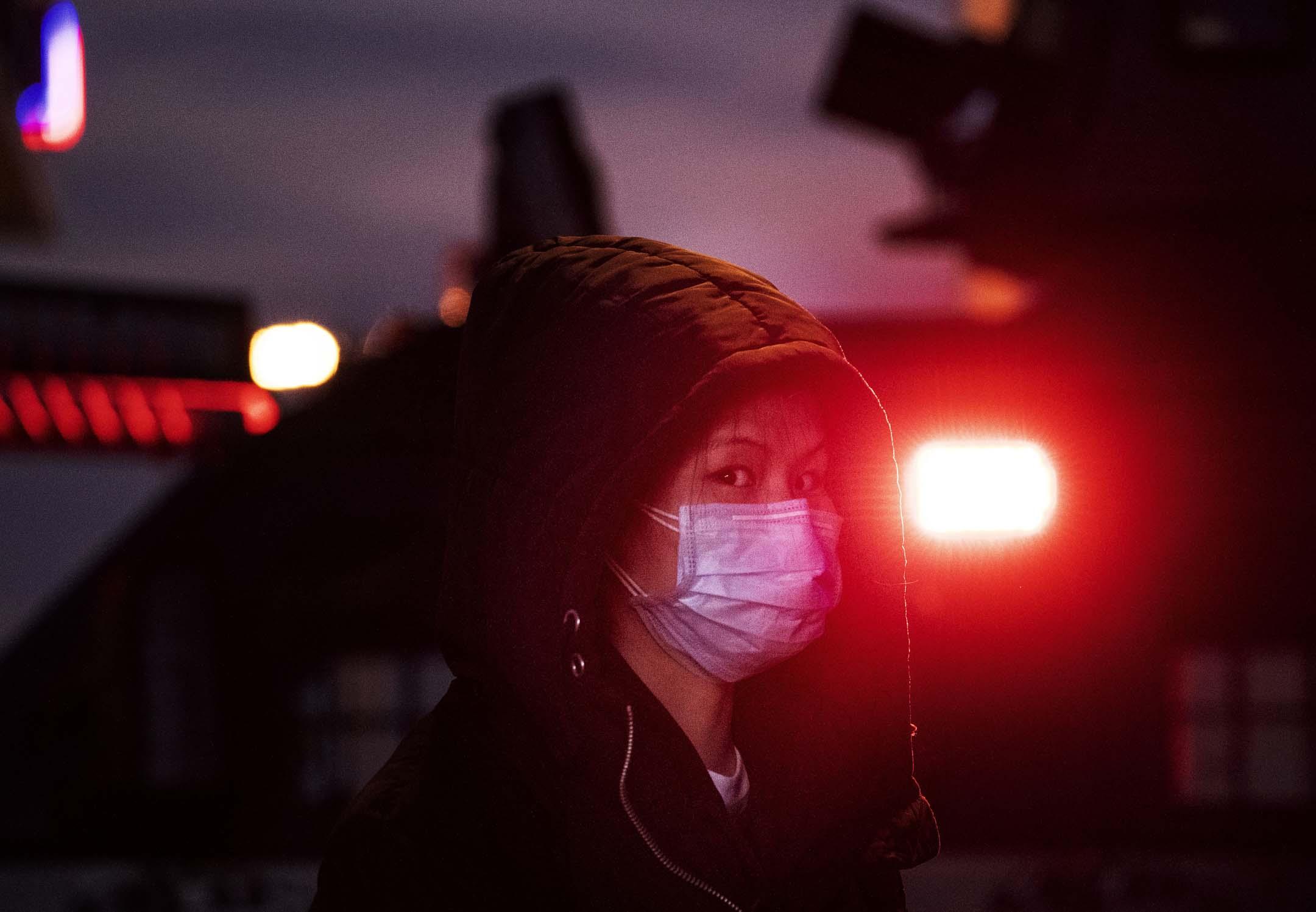 2020年1月21日,春節前夕,一名戴著口罩的女士站在北京火車站一架警車的旁邊。
