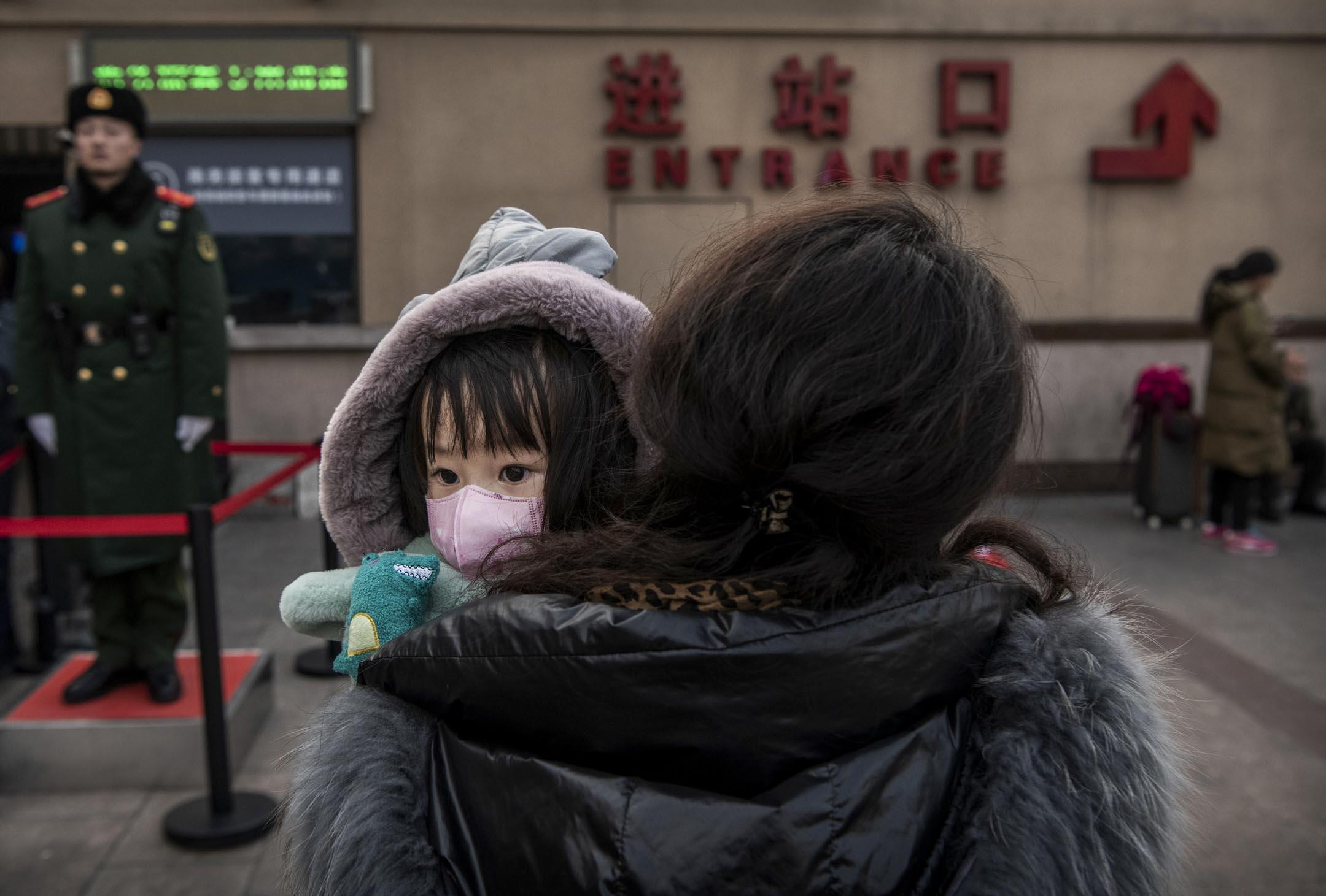 2020年1月21日,在春節夕的北京火車站,一名中國女孩戴著防護口罩,等候登車。