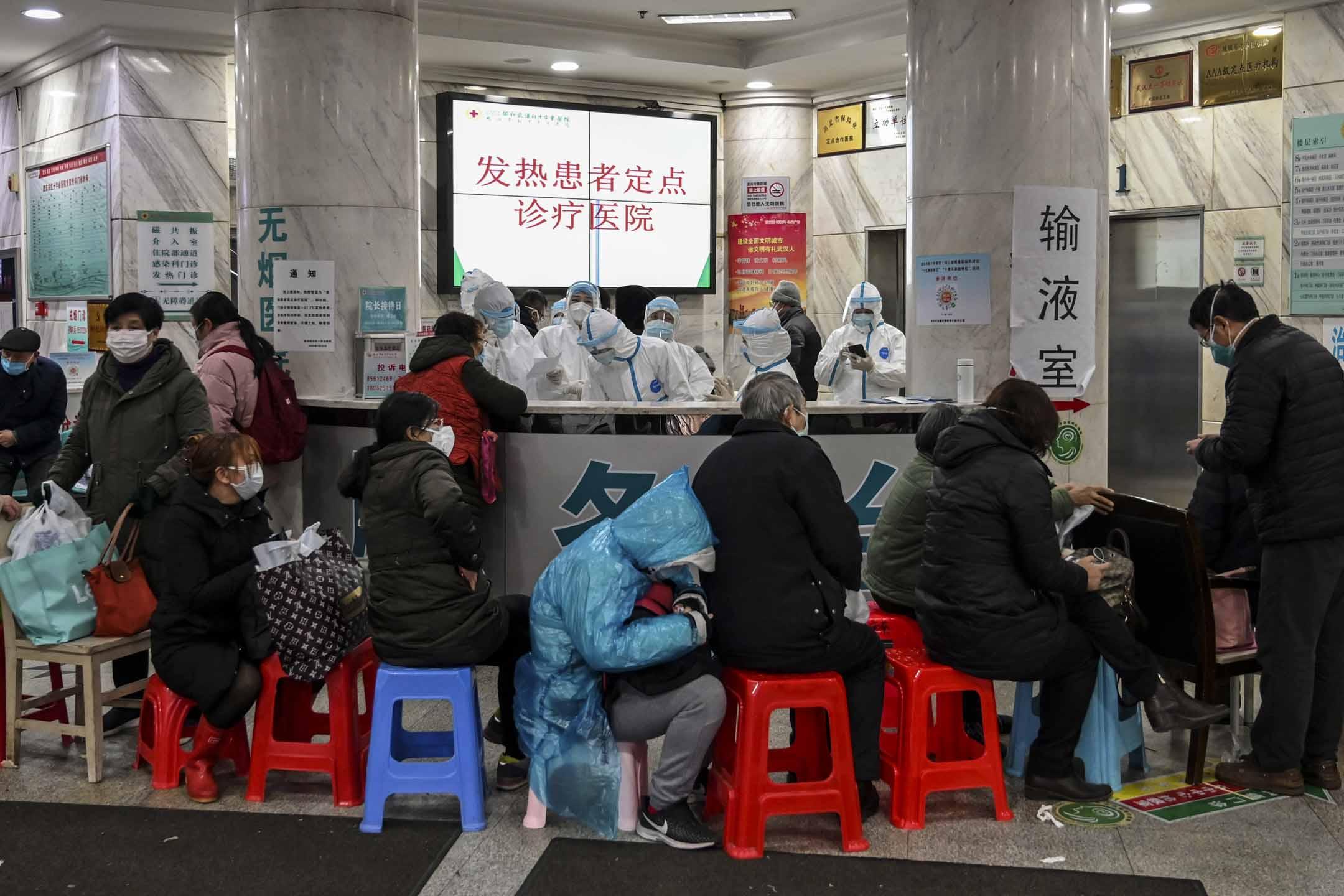 2020年1月24日,武漢市紅十字會醫院,穿著防護服的醫務人員及等候的病人。