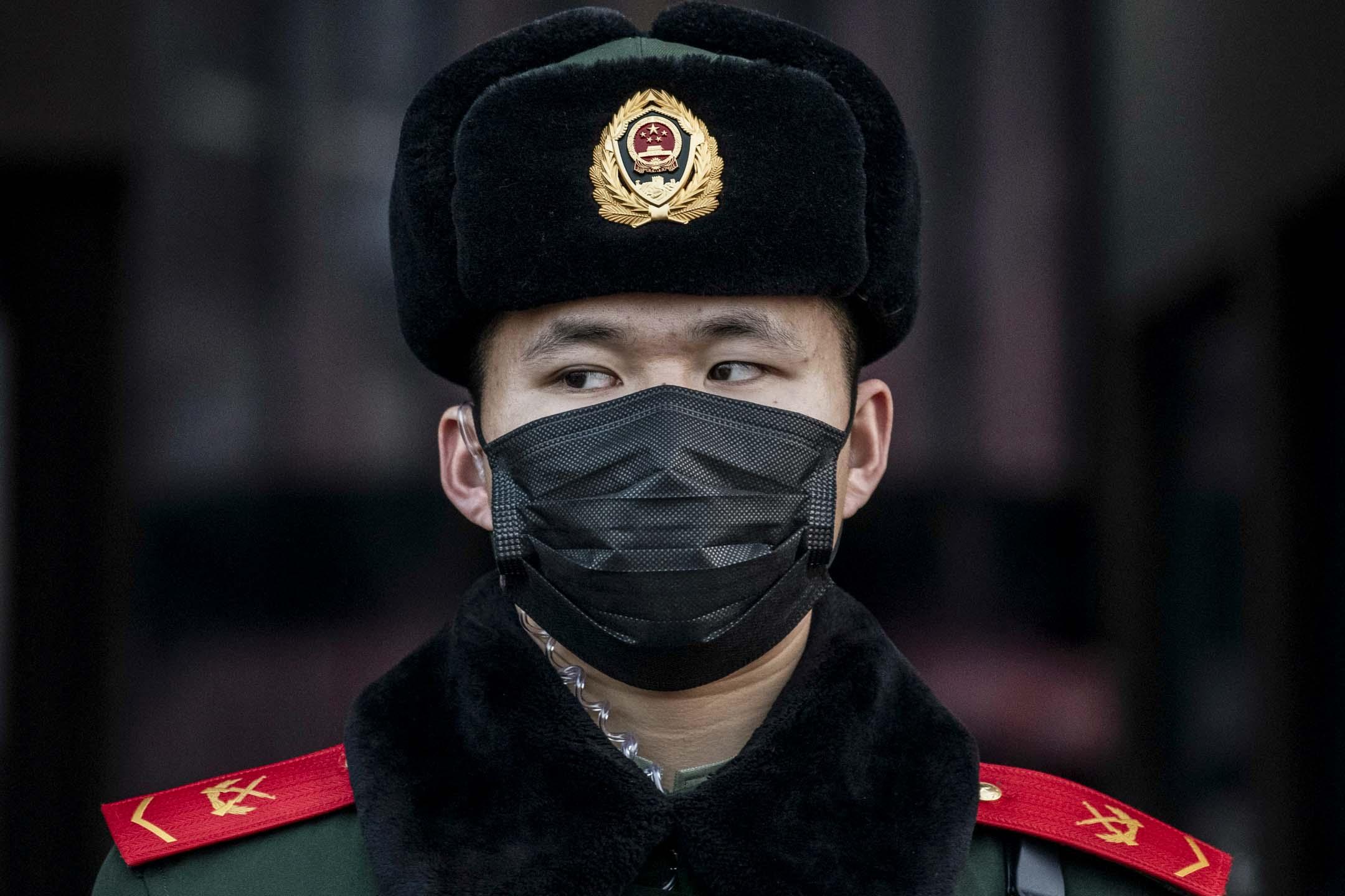 2020年1月22日,春節前夕,一名中國警官在北京火車站站崗時戴著口罩。  攝:Kevin Frayer/Getty Images
