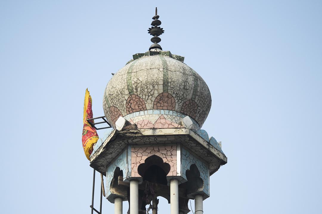 2020年2月26日在印度首都新德里,印度教徒與穆斯林之間的衝突持續,一座清真寺的宣禮塔被懸掛起印度教旗幟,清真寺則被焚毁。 攝:Sajjad Hussain / AFP via Getty Images