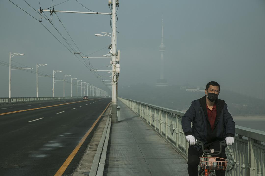 武漢一名戴著口罩的男士騎著單車在武漢長江大橋上。
