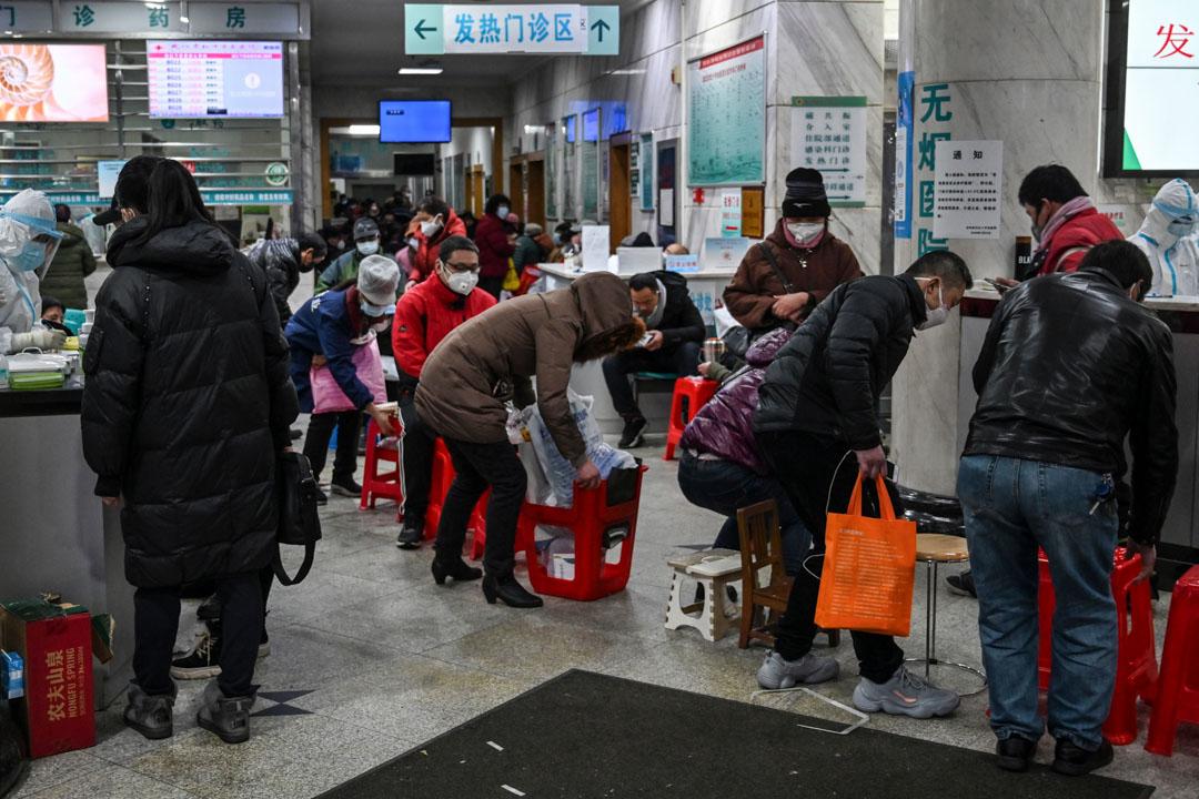 2020年1月25日,戴著口罩的病人在武漢紅十字會醫院等待醫療救助。