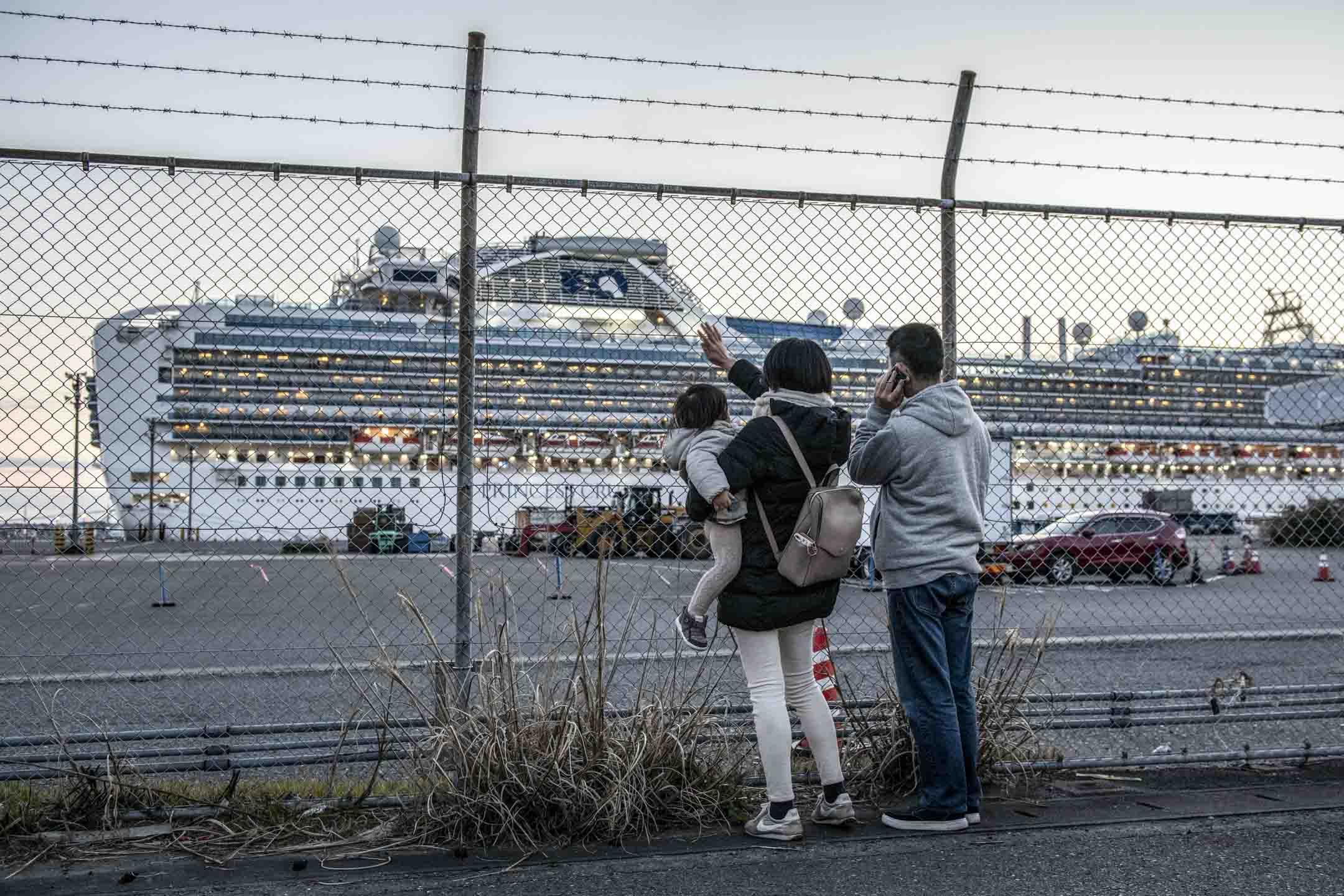 2020年2月11日,日本橫濱市一家人向停泊在岸的鑽石公主號揮手。郵輪因新冠疫情在船上爆發,於2月4日起在橫濱隔離大約一個月。最終超過700人被感染,12人死亡。