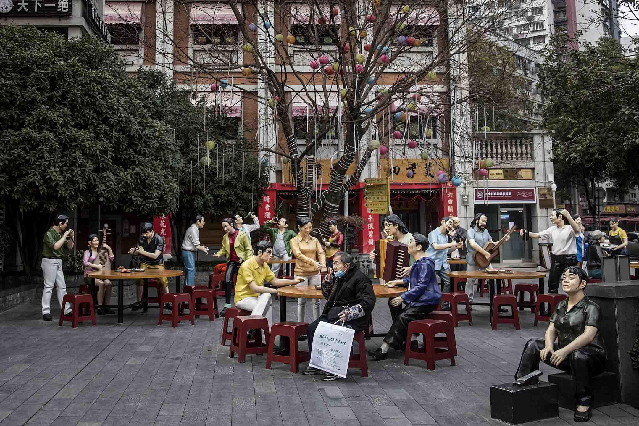 2020年2月8日,武漢一名長者坐在飲食文化街上的雕塑旁。
