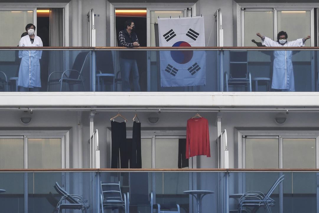 2020年2月14日,鑽石公主號上的乘客站出陽台向岸上的人招手。