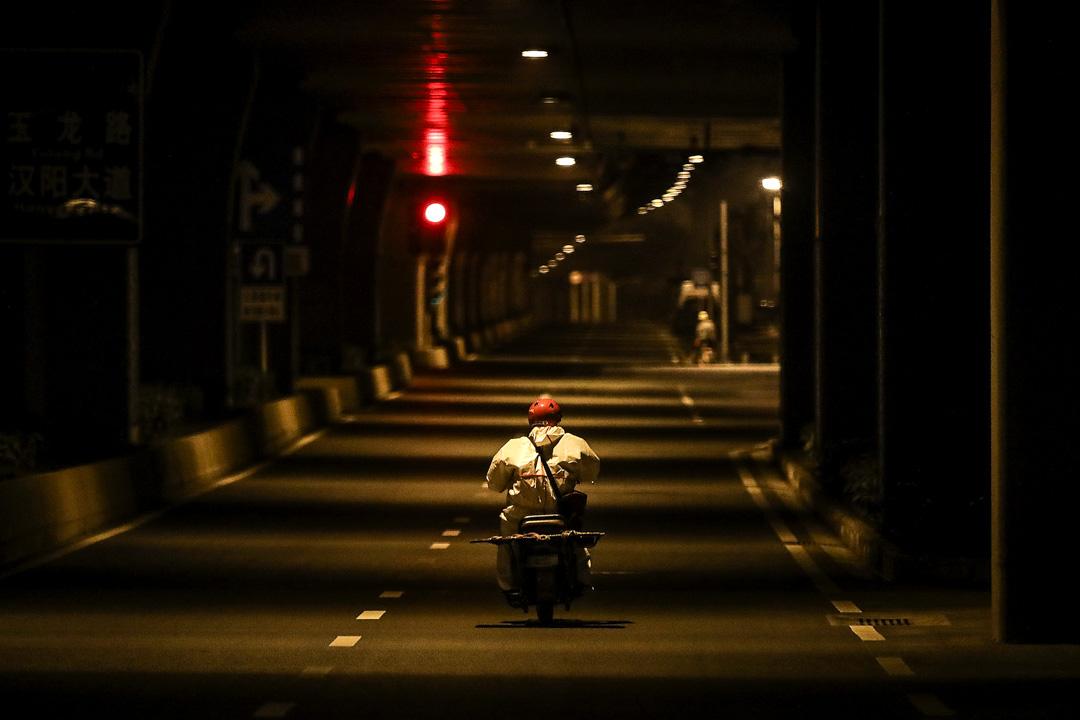2020年2月1日,一名快遞員在武漢市一條街道上騎著自行車運送包裹。  攝:Stringer/Getty Images
