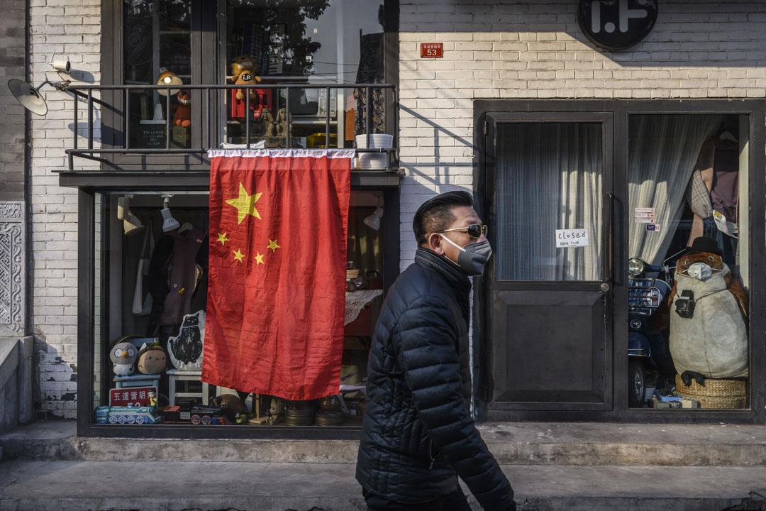 2020年2月19日,北京一個男子戴著口罩在國旗前經過。