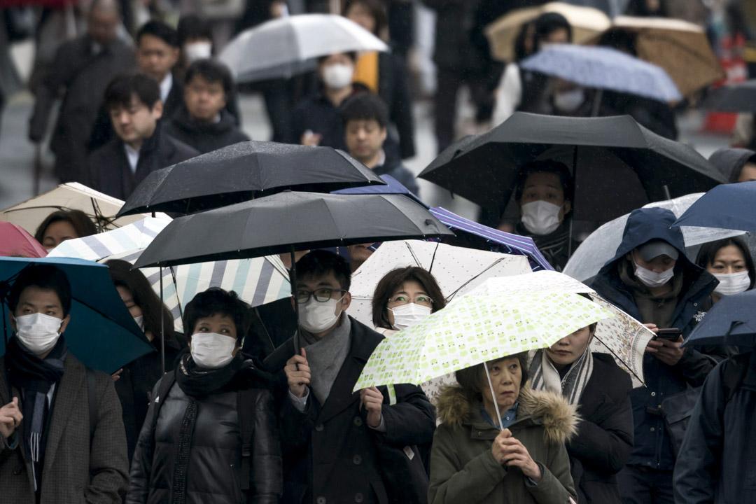 2020年2月13日,東京,戴著口罩的市民拿著傘步行在路上。