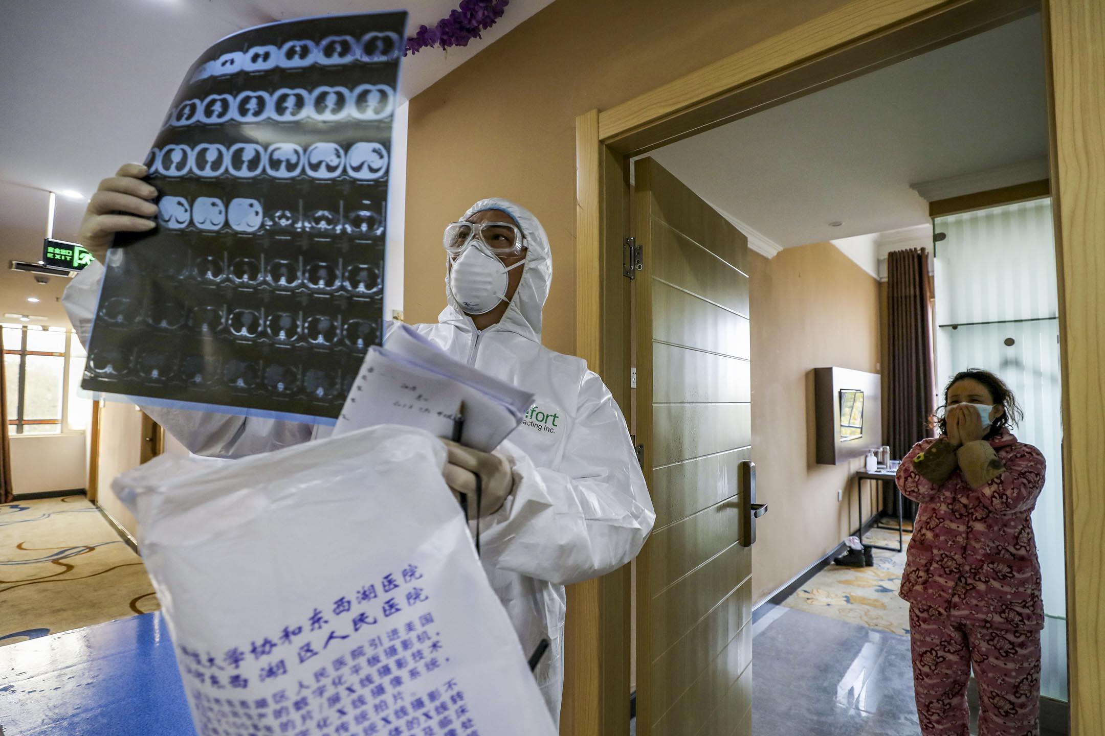 2020年2月3日,武漢市隔離區的一間病房裡,醫護人員巡視病房並查看隔離人士的肺部CT圖像。 攝:STR/AFP via Getty Images