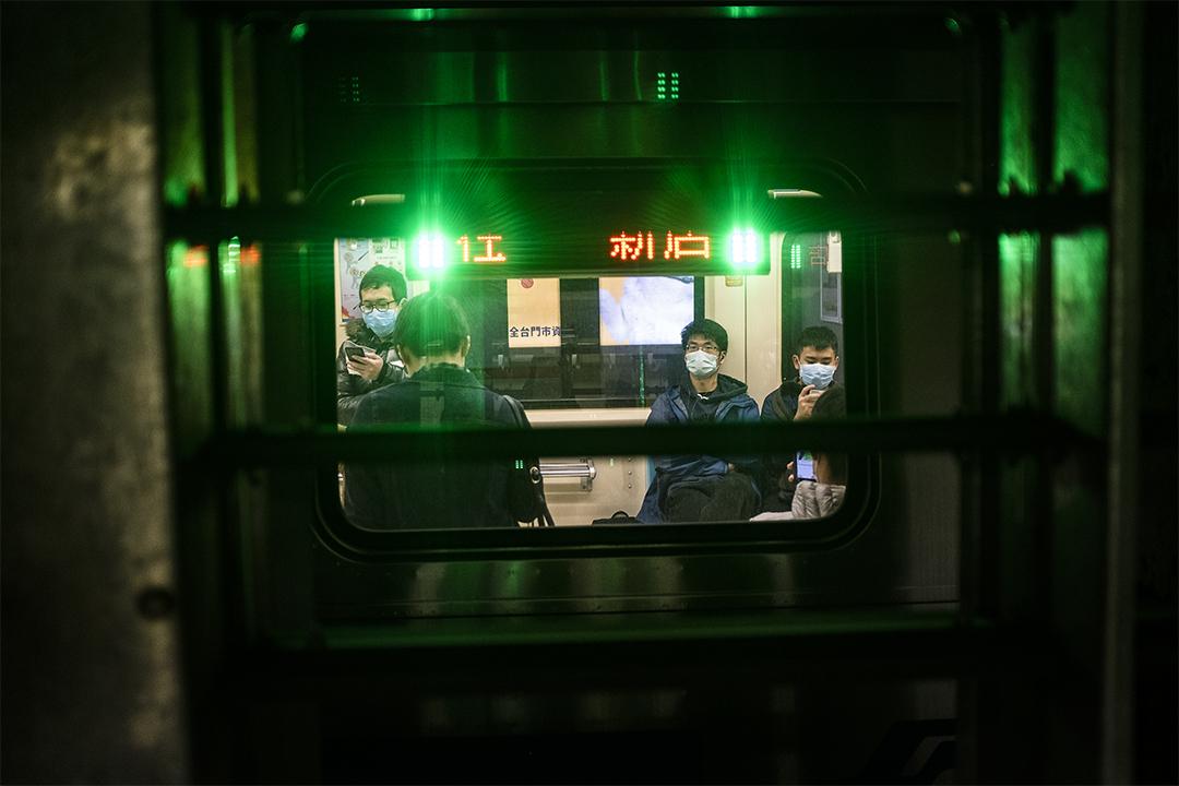 台北捷運內的乘客戴上口罩。