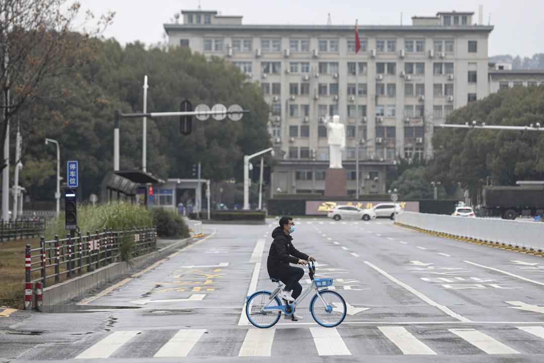 2020年2月7日,中國武漢的市民戴著口罩踏單車。