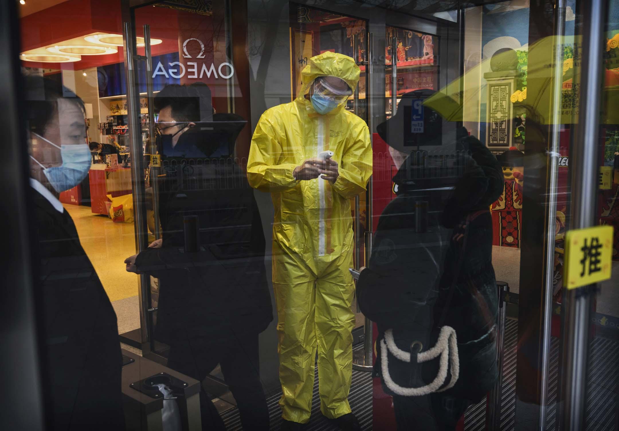 2020年2月14日,北京的一個購物區,穿著防護服的工作人員檢查入內客人的體溫。 攝:Kevin Frayer/Getty Images