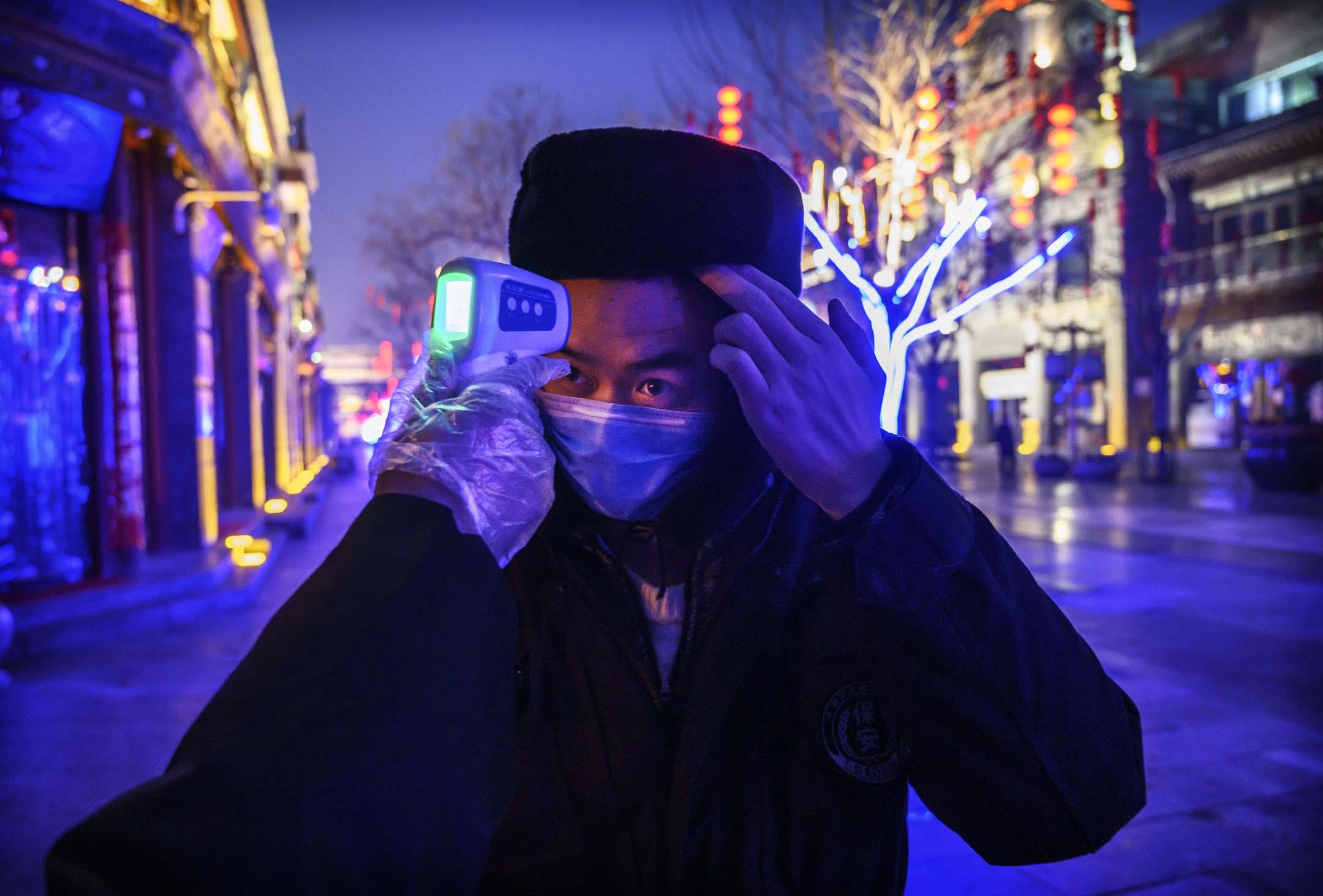 2020年2月12日,北京一條空曠的商業街上,一名戴著防護口罩的工人正被檢測體溫。  攝:Kevin Frayer/Getty Images