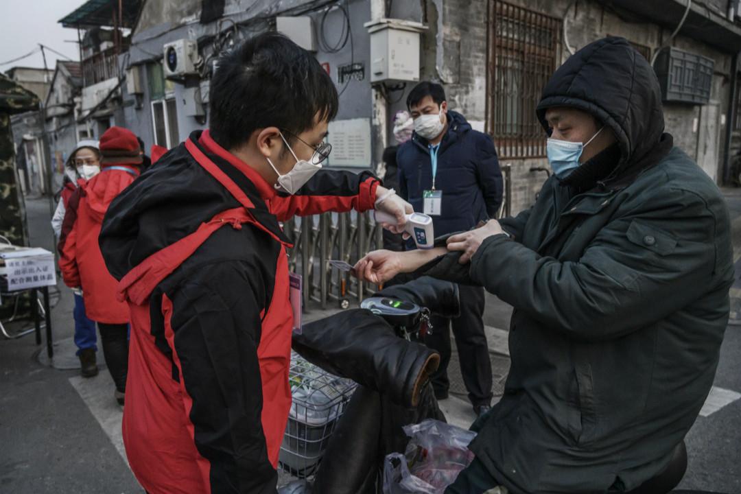 2020年2月19日,北京,居民在街頭被檢測體溫。 攝:Kevin Frayer/Getty Images