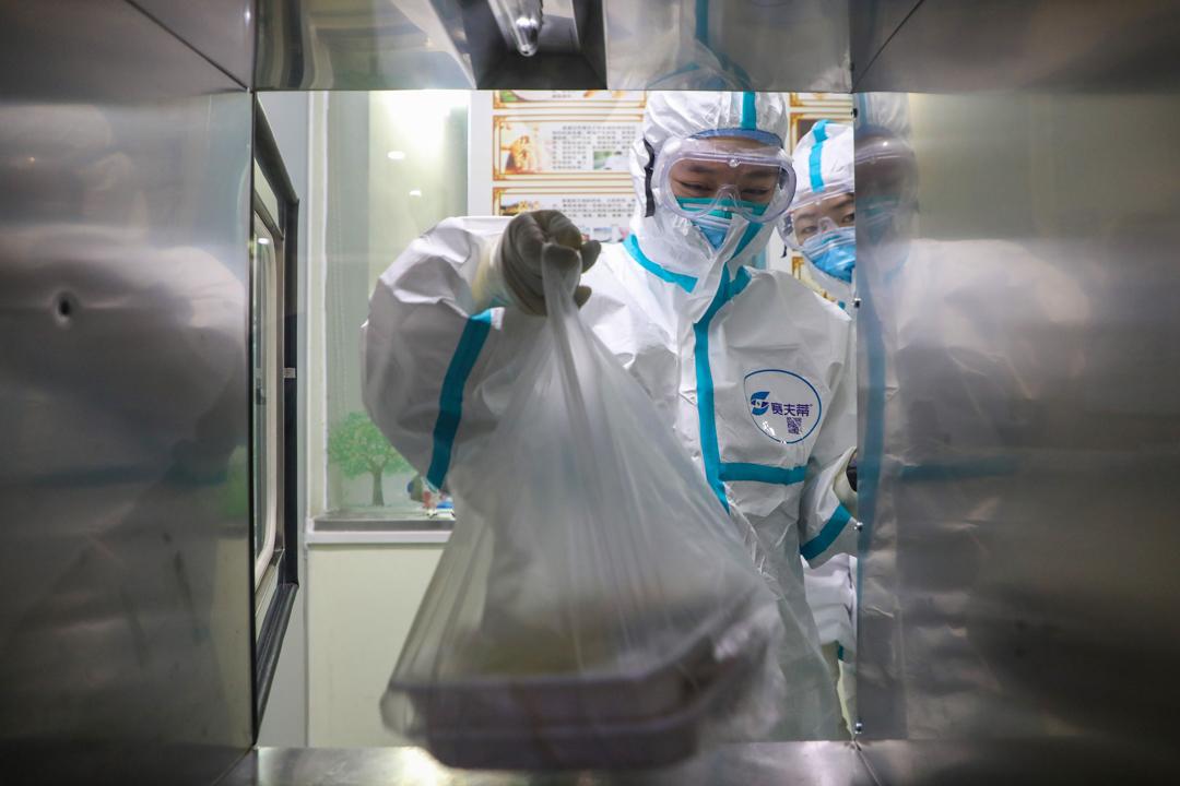 2020年1月30日,武漢醫院內的醫護正在遞送飯盒給隔離病房中的病人。
