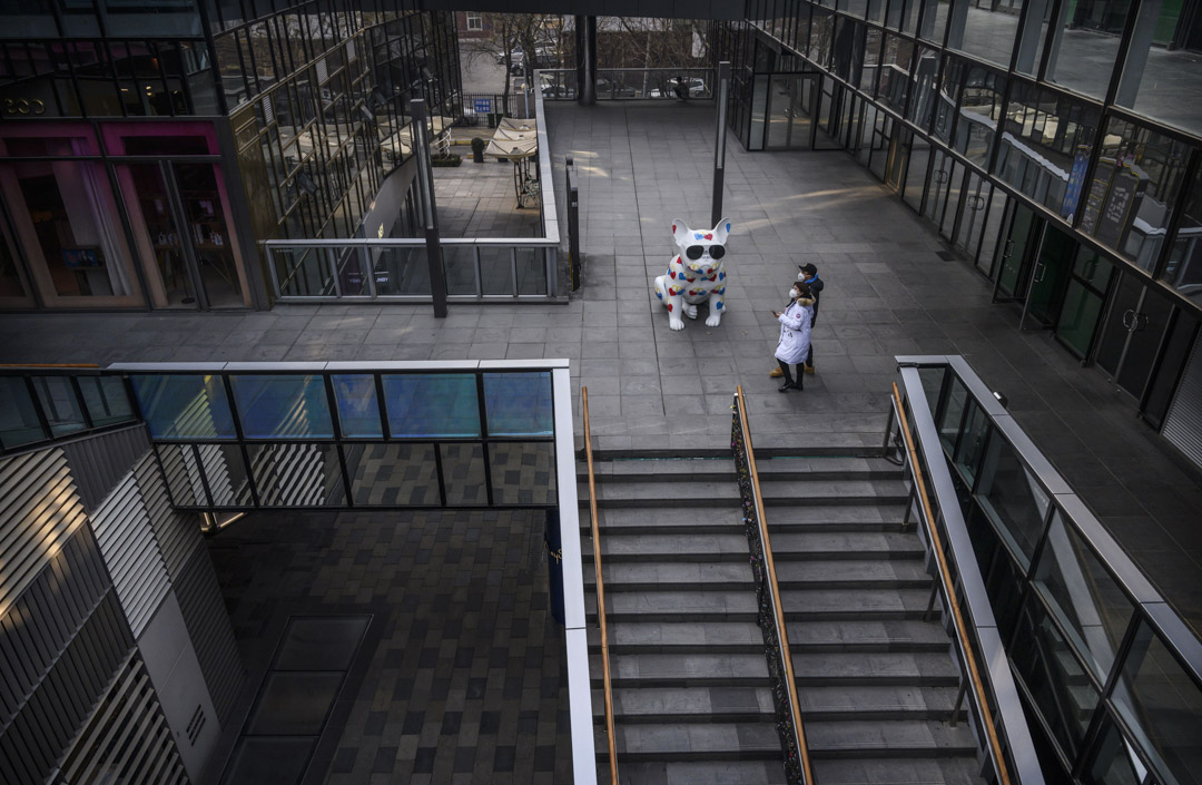 2020年1月28日,北京戴著防護口罩的一對夫婦在空蕩蕩的購物區行走。