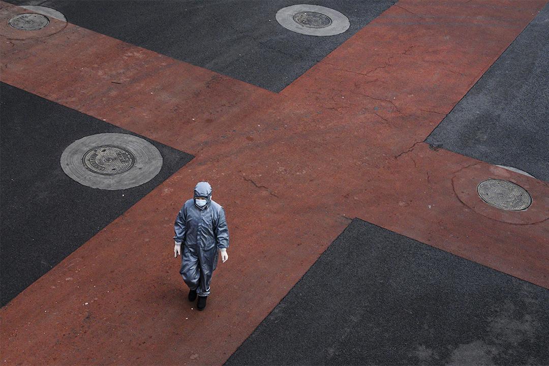 2020年2月8日一名中國婦女穿著防護衣服和面罩在北京穿過一條空的街道。