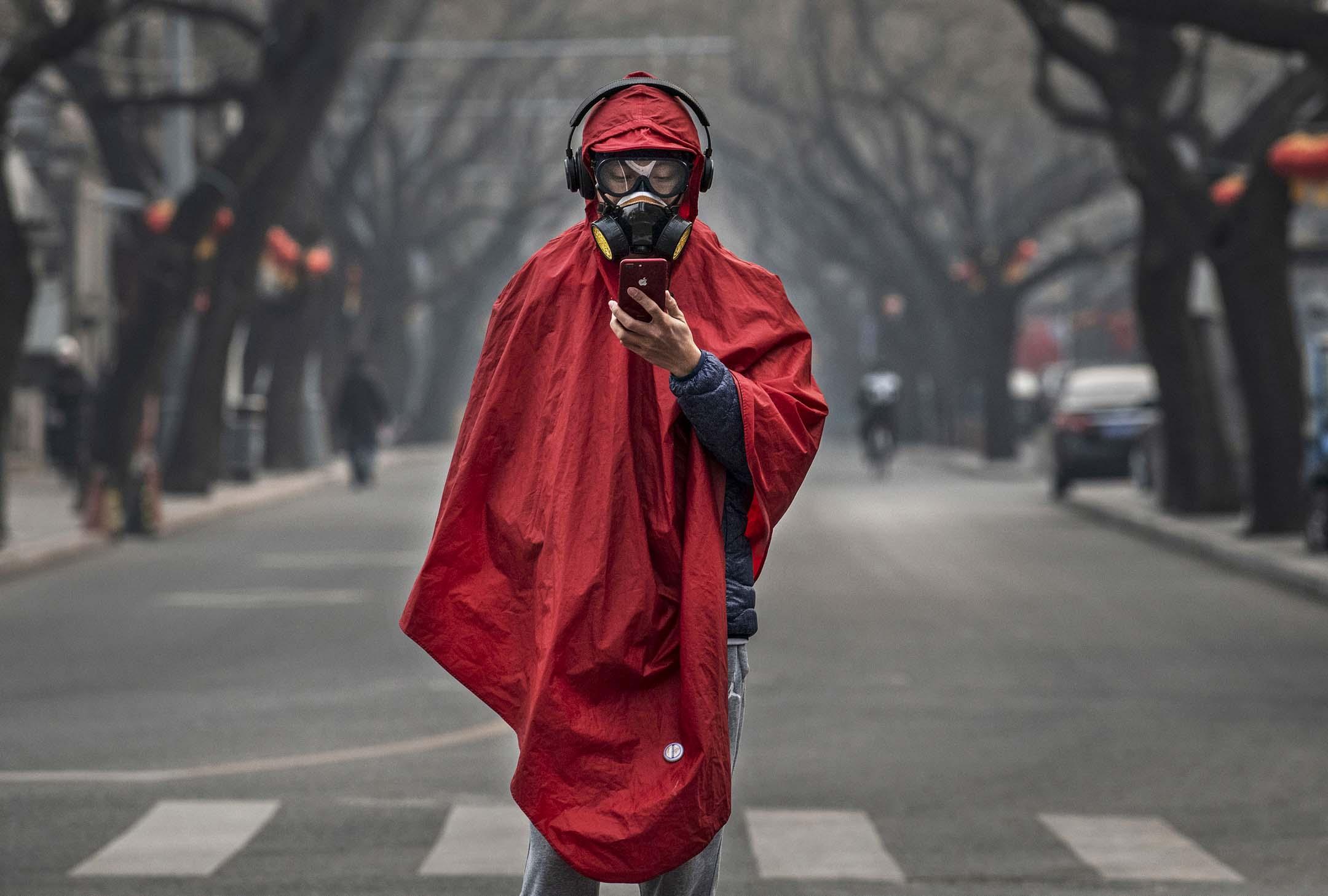 2020年1月26日,中國北京的農曆新年假期,一名戴著防護面具、護目鏡和紅色大衣的中國男子在一條空曠的街道上。 攝:Kevin Frayer/Getty Images