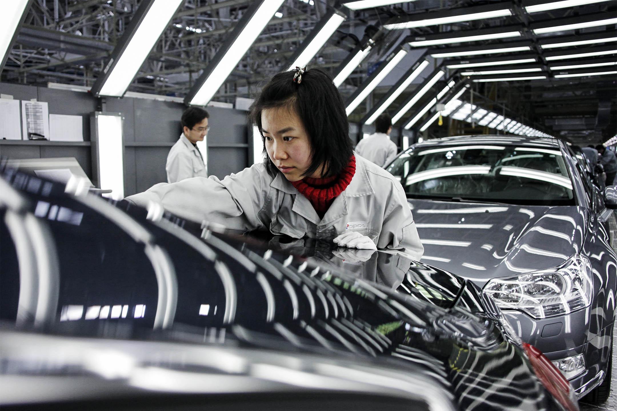 2009年11月24日,工人於中國湖北省武漢市的汽車工廠生產線上工作。 攝:In Pictures Ltd./Corbis via Getty Images