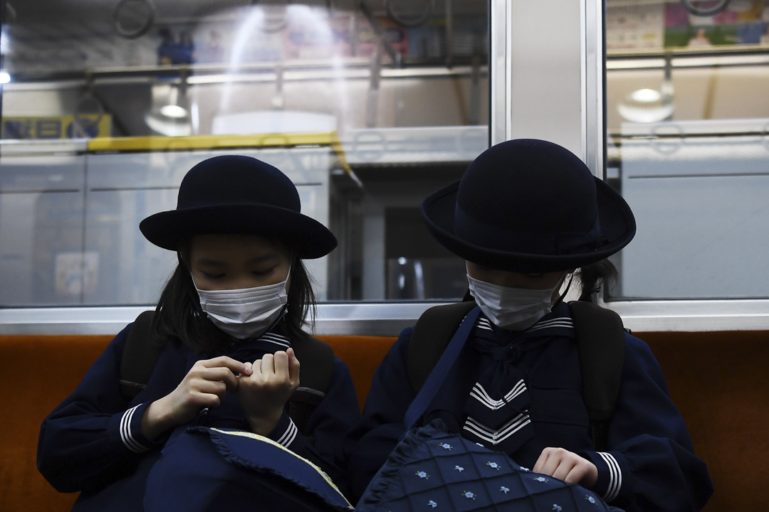 2020年2月13日,戴著口罩的女學生在東京的火車上。