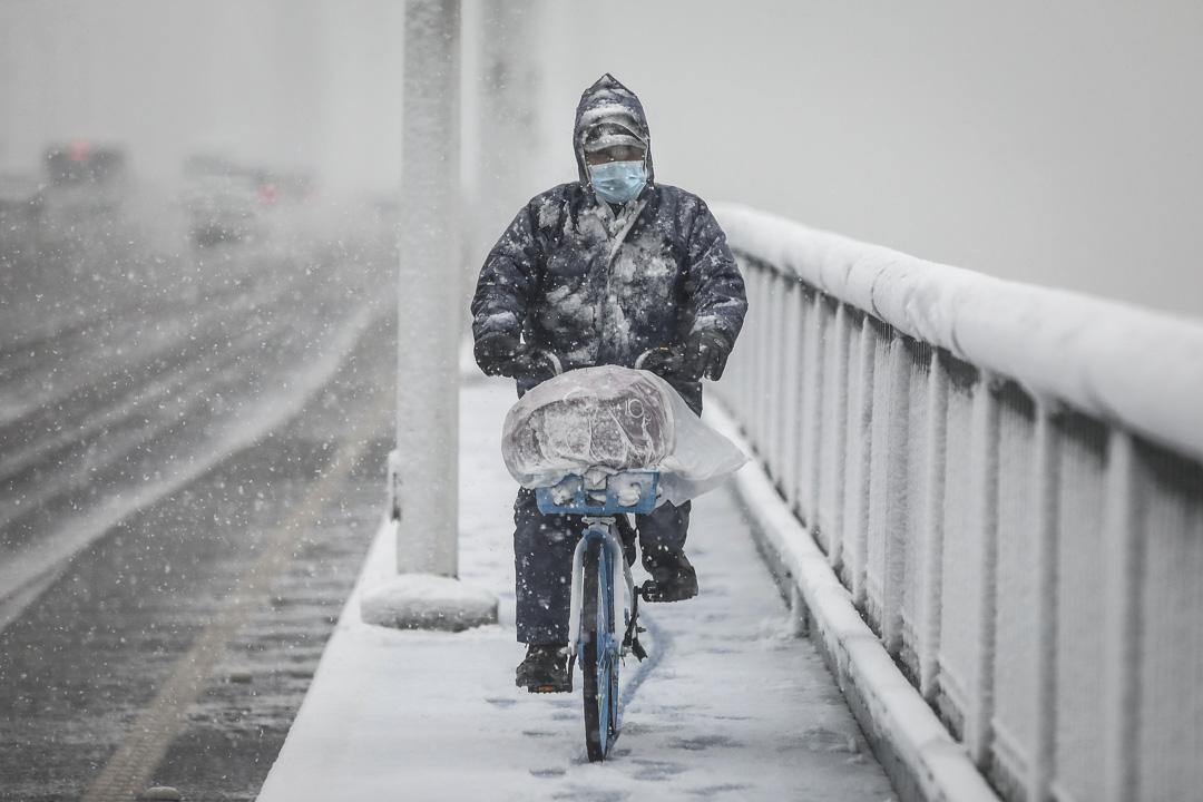 2020年2月15日,武漢大雪,一個戴著口罩的人騎著單車穿過大橋。