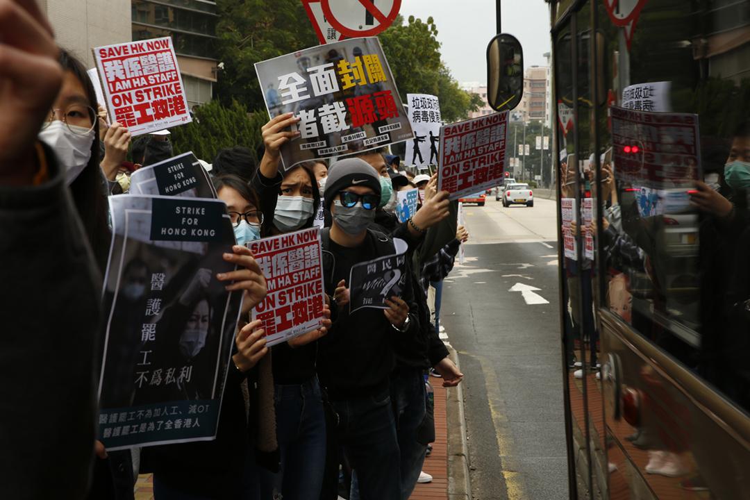 2020年2月7日在香港醫院管理局大樓外,有參與罷工的「醫管局員工陣線」成員於馬路旁展示標語,希望路過市民理解醫護罷工所爭取的訴求。 攝:林振東 / 端傳媒