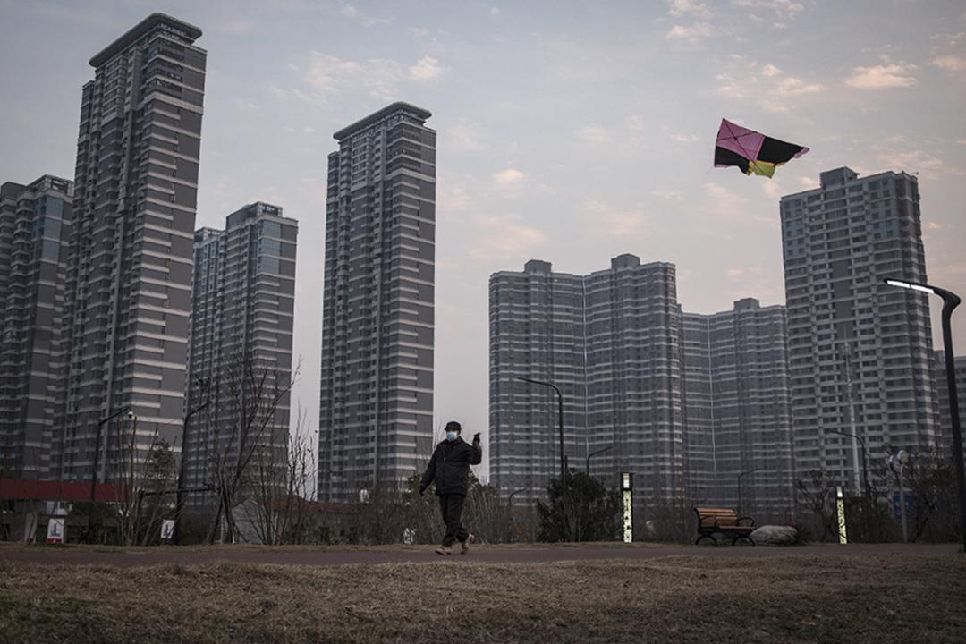 2020年2月10日,一個中國男子戴著口罩獨自一人在中國北京的辦公室大樓前放風箏。