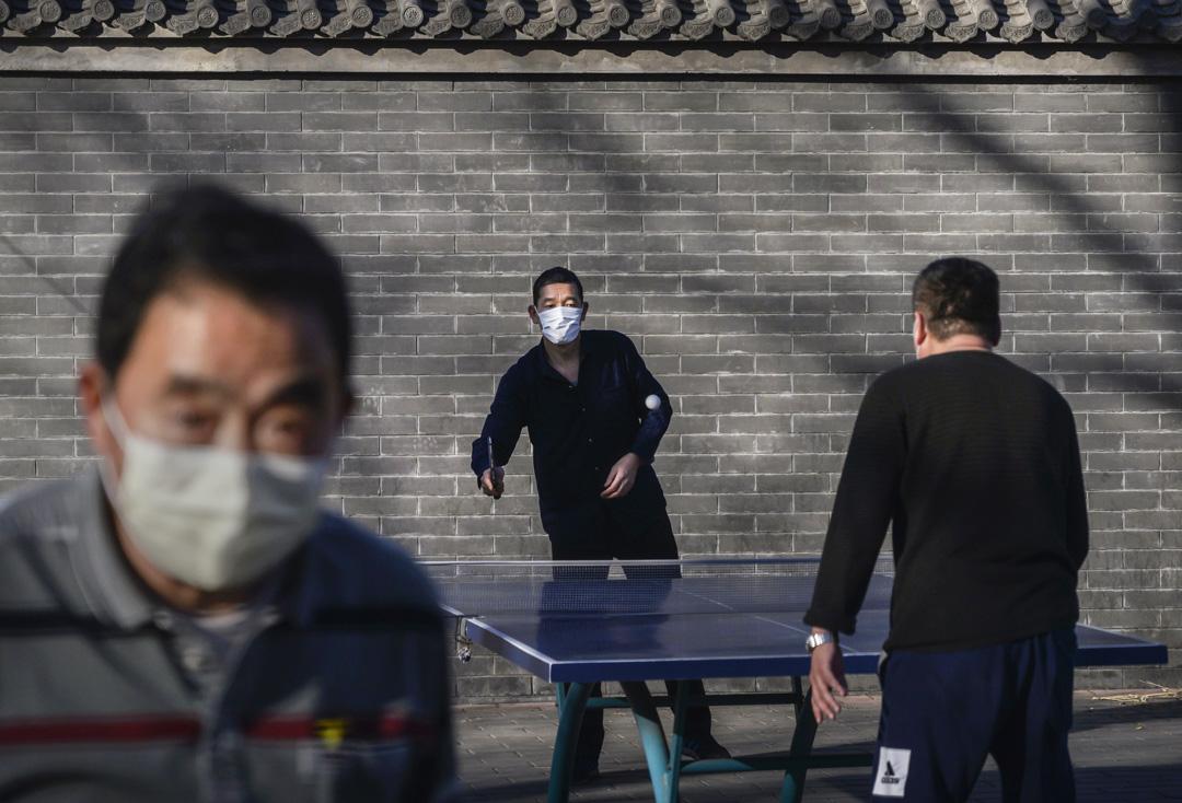 2020年2月17日,北京市民戴著口罩在公園打乒乓球。