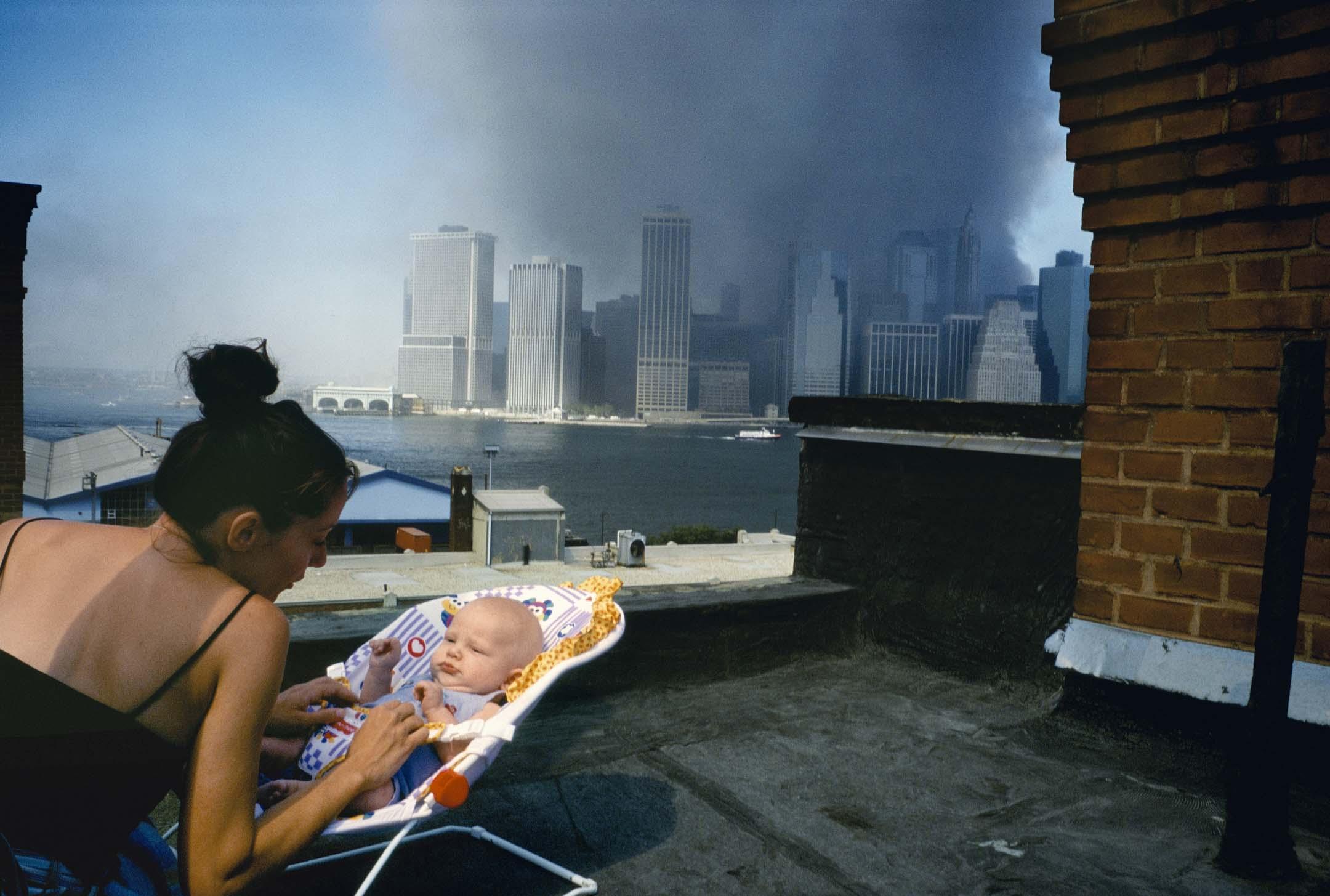 2001年9月11日,一名母親在紐約布魯克林的一個屋頂上輕輕安慰孩子。 圖:Alex Webb / Magnum Photos