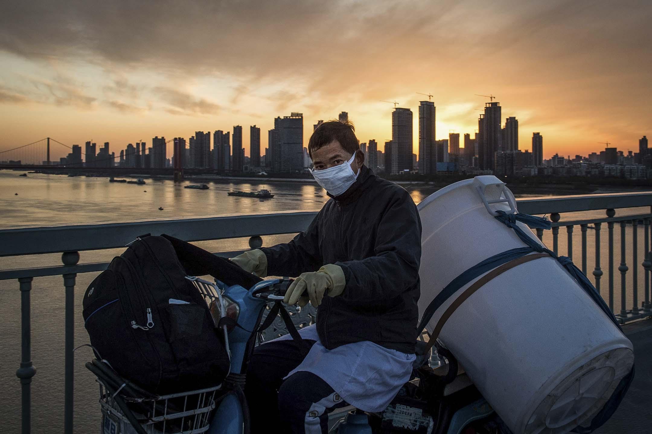 2020年2月17日,一名戴著防護口罩的男士在武漢市騎單車。 攝:STR/AFP via Getty Images