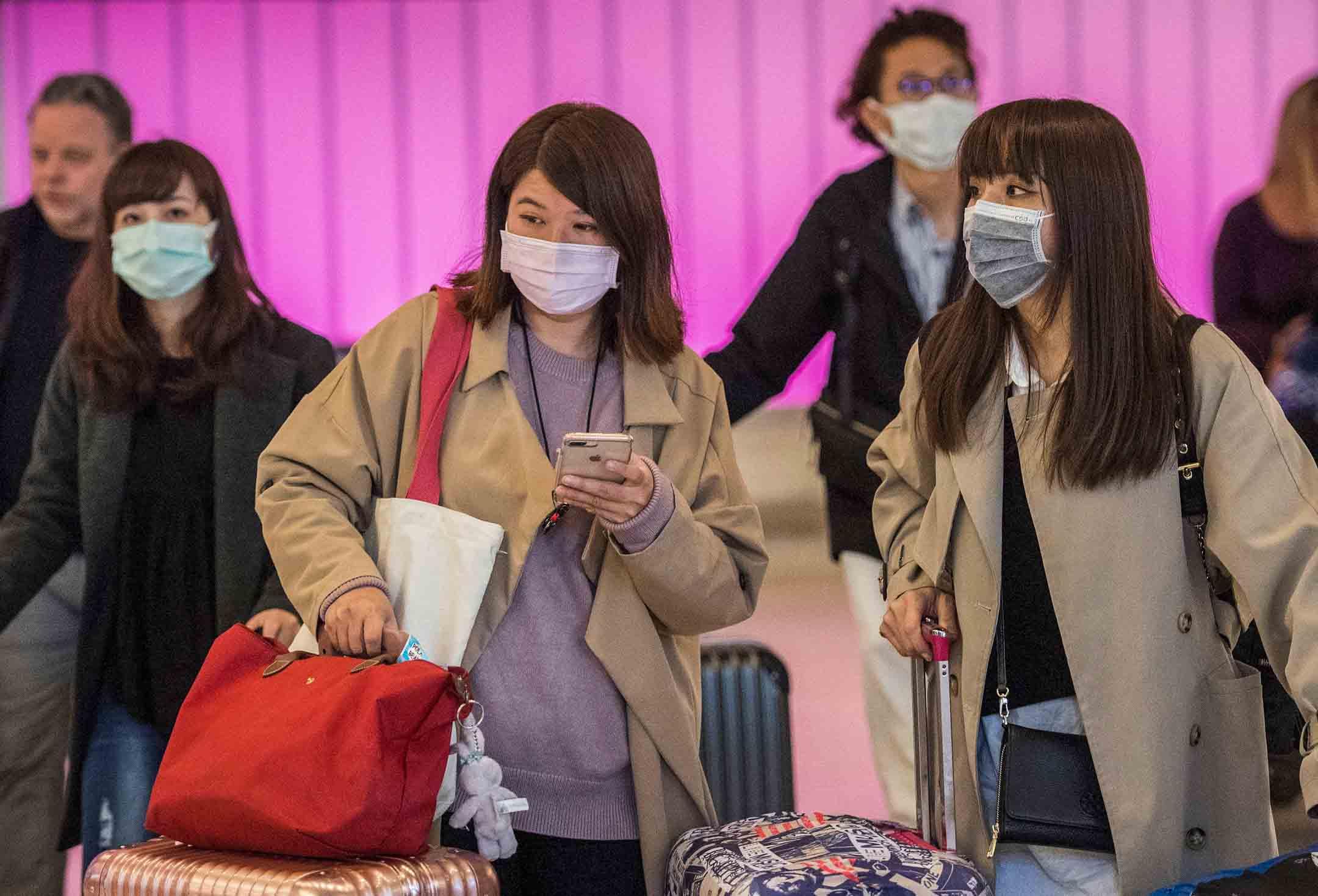 2020年1月22日,洛杉磯國際機場,乘客到達時都戴著口罩。 攝:Mark Ralston/AFP via Getty Images