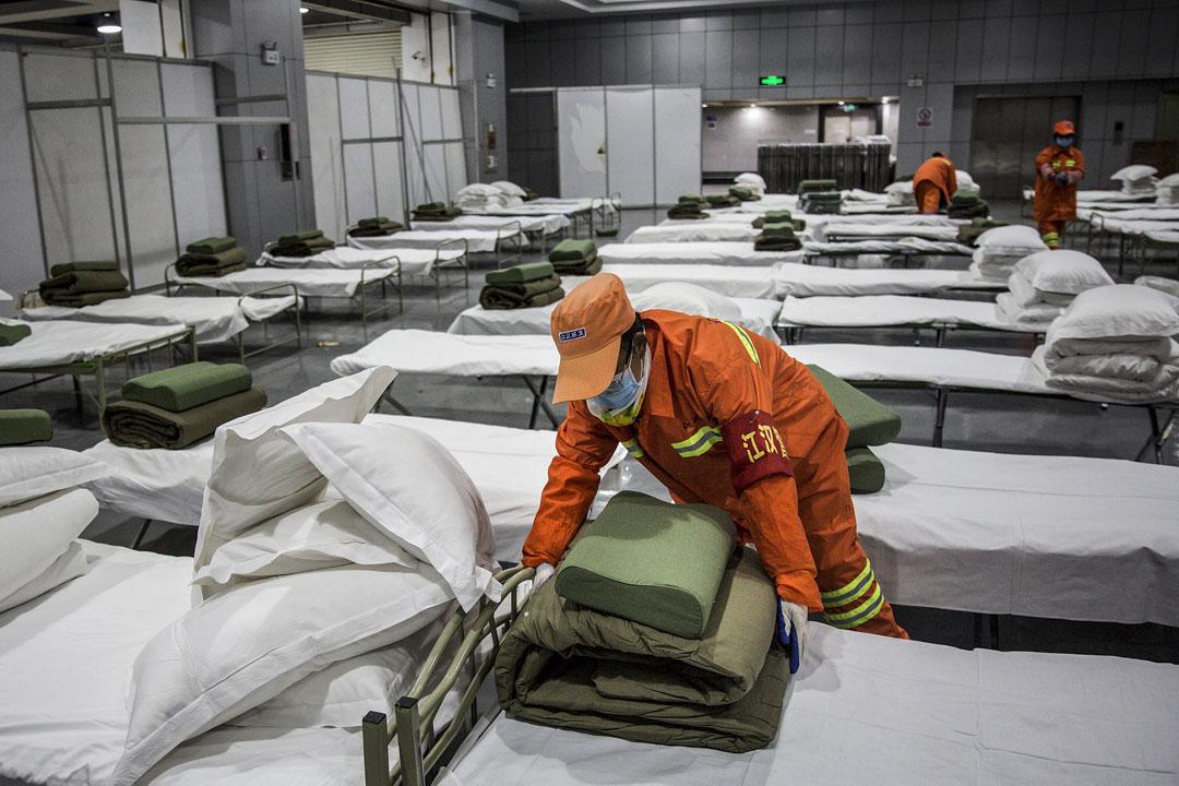 2020年2月4日,武漢市以體育館改裝而成的臨時醫院內,工作人員正在整理病床。