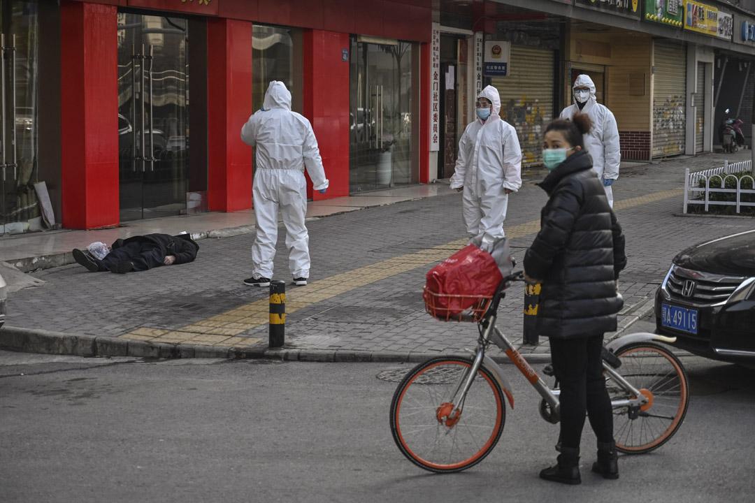 2020年1月30日,武漢一家醫院附近,穿著防護服的政府人員查看一名倒在街上已過世的老人。