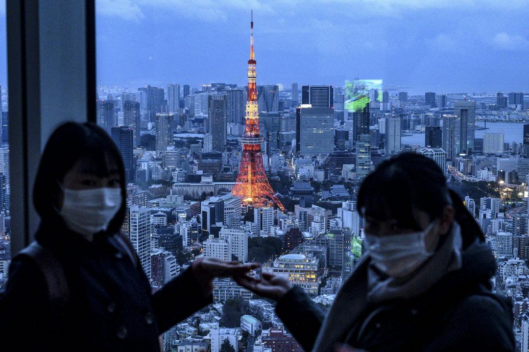 2020年2月22日,東京鐵塔在黃昏時分亮起,人們戴著口罩在觀景台合影。 攝:Philip Fong/AFP via Getty Images