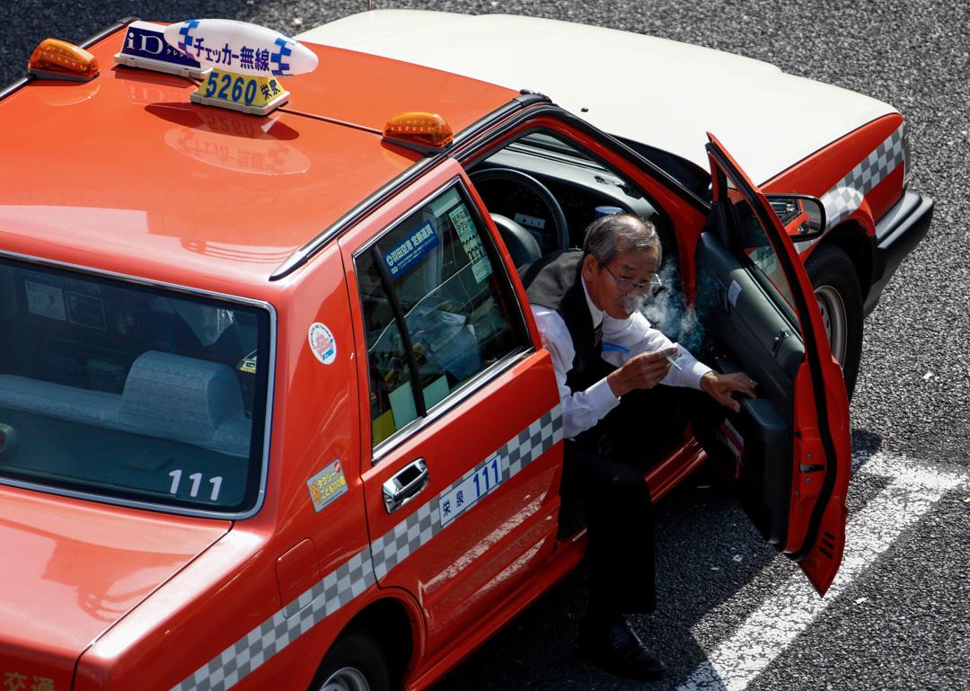 日本一名年長的計程車司機踏出車外。 攝: Tomohiro Ohsumi/Bloomberg via Getty Images