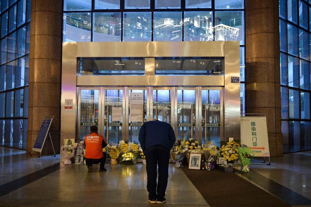 2020年2月7日,武漢醫院後湖分院外,一名男子在鮮花面前鞠躬,紀念已故的眼科醫生李文亮。