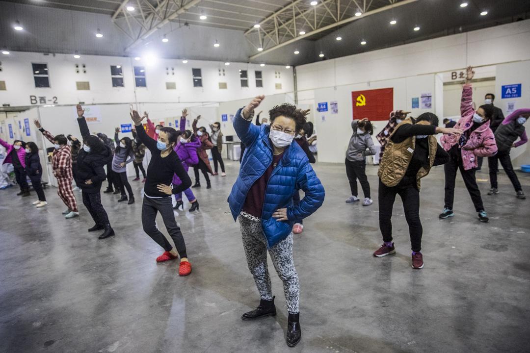 2020年2月17日,呈新冠病毒症狀的患者在武漢一個臨時醫院內做運動。 攝:STR/AFP via Getty Images