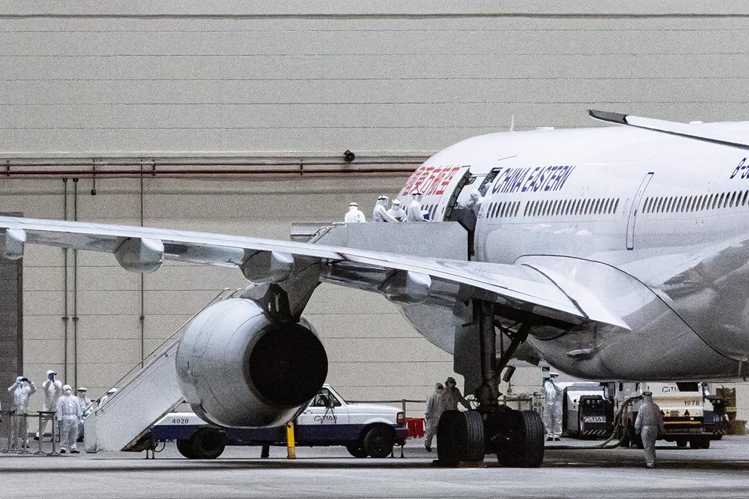 2020年2月3日桃園國際機場,武漢台商午夜抵達機場,飛機直接進入維修棚,醫護人員上機檢疫後安置隔離。