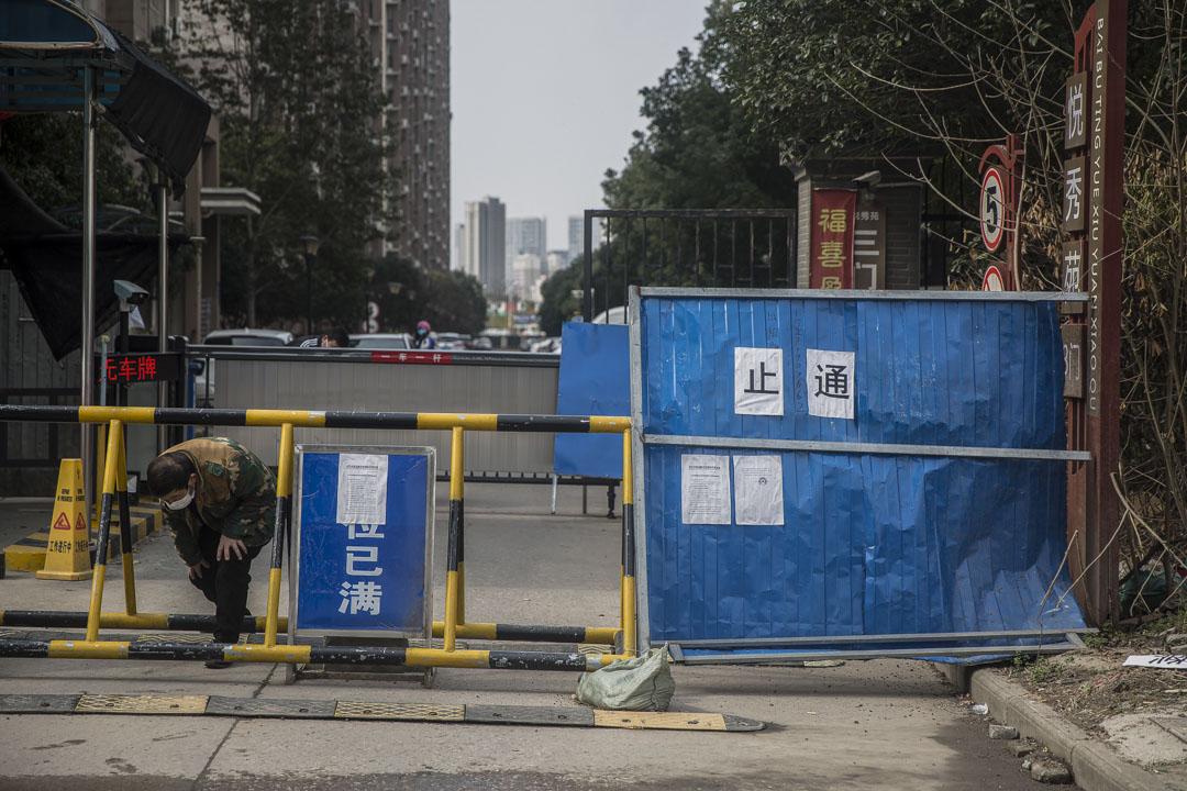 百步亭悅秀苑小區,一位快遞員把包裹放在門口後鑽出路障。
