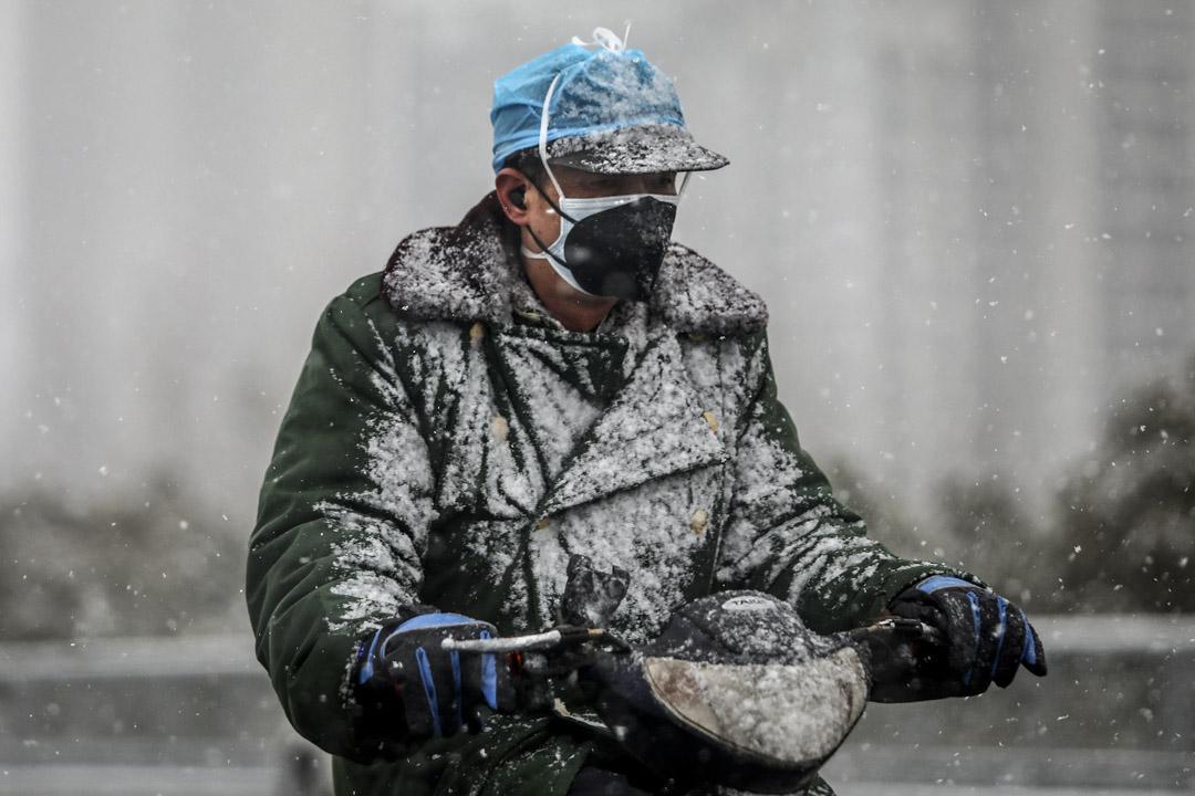 2020年2月15日,武漢一名司機在大雪中騎著電單車。