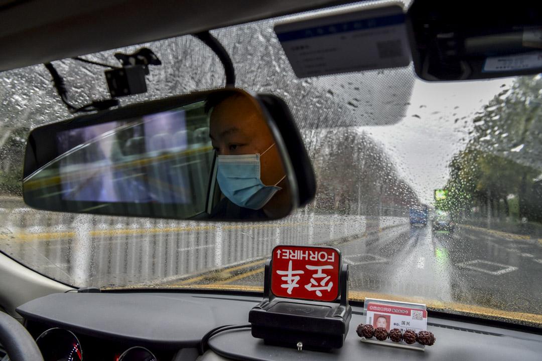 2020年1月25日,戴著口罩的士司機在武漢的街上行走。