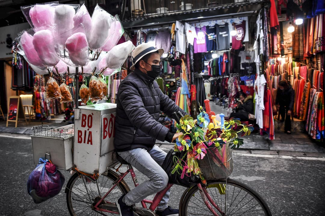 2020年2月6日,越南河內一名小販戴著口罩在街上騎腳踏車。