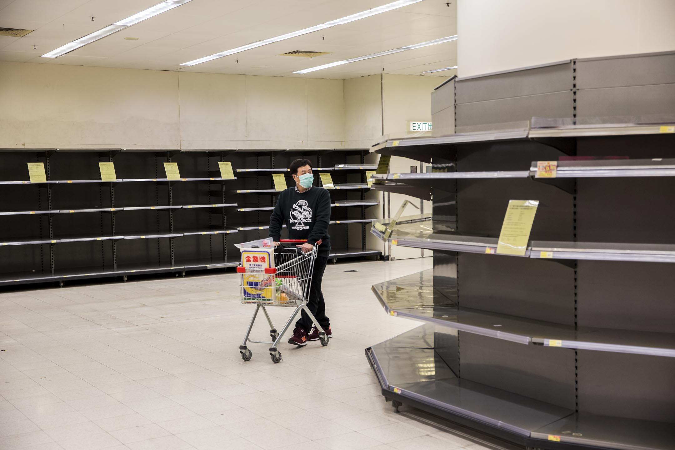2020年2月7日,香港一間超市的日用品被搶購一空,已購買一包米的市民在貨架之間。 攝:林振東/端傳媒